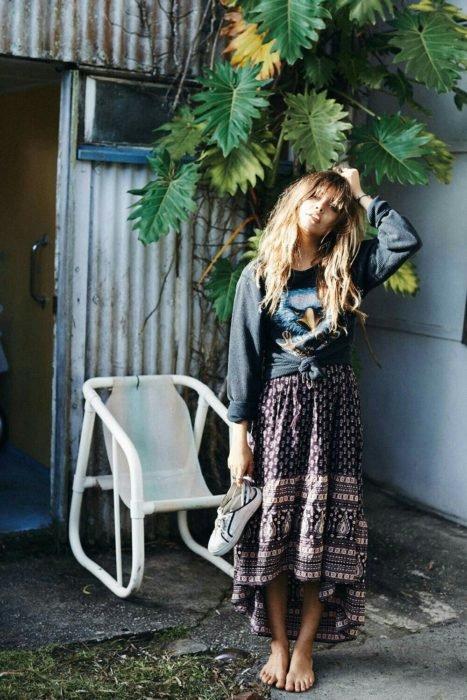 Ropa estilo boho o hippie chic; mujer parada frente una planta, de cabello castaño largo, con sudadera oversized, maxi con los tenis blancos en las manosfalda