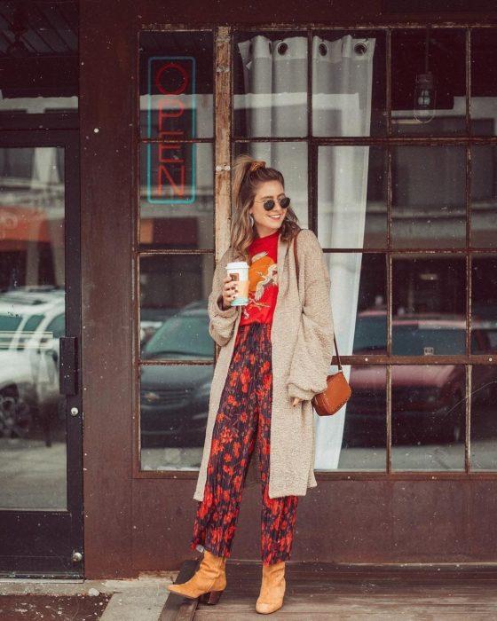 Ropa estilo boho o hippie chic; chica con peinado de media cola alta con dona, lentes de sol, playera roja de gruyas, abrigo largo, pantalón holgado floreado con botines cafés