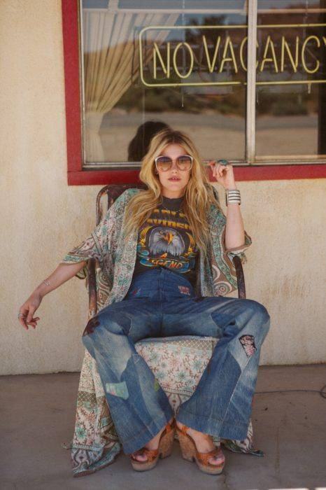 Ropa estilo boho o hippie chic; chica rubia sentada en una mecedora, con playera con estampado de águila, pantalón acampanado de mezclilla