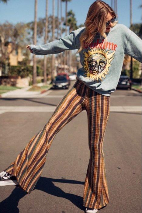 Ropa estilo boho o hippie chic; chica en la calle con pantalón acampanado de rayas verticales con sudadera gris con estampado de sol