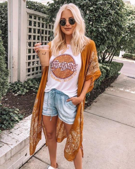 Ropa estilo boho o hippie chic; chica de cabello rubio platinado, con lentes de sol redondos, con playera de Aerosmith, short de mezclilla y chal de paliacate amarillo, con un café helado