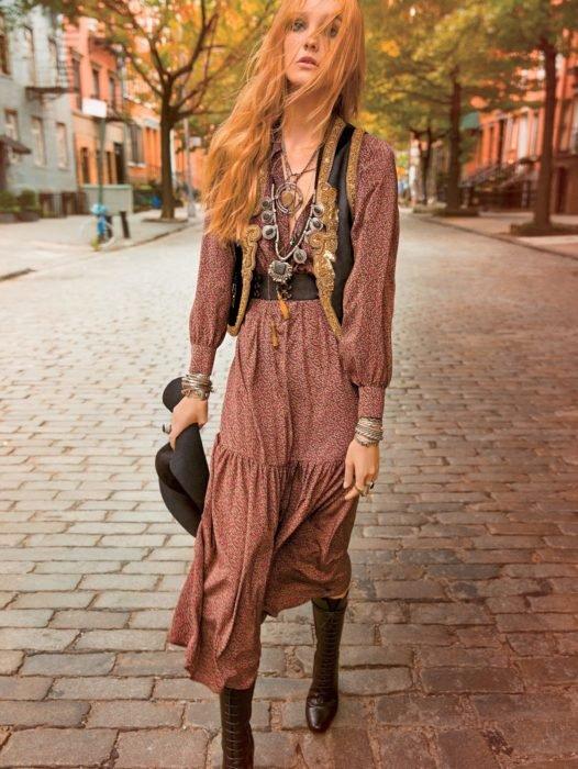 Ropa estilo boho o hippie chic; mujer de cabello largo y pelirrojo en calle empedrada con vestido de flores, cinto, con chaleco, pulseras y collares