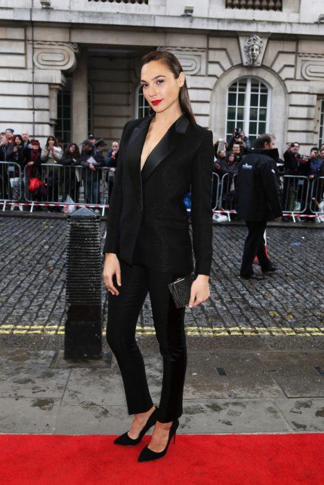 Famosas con traje; Gal Gadot con saco y pantalón de gala negro, zapatillas stiletto y bolsa de mano