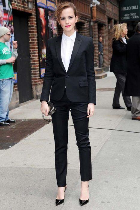 Famosas con traje; Emma Watson en la calle con saco y pantalón de vestir, zapatillas, bolsa de mano y el cabello recogido en una cola de caballo