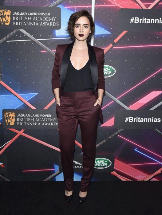 Famosas con traje; Lily Collins en los British Academy Britannia Awards con saco y pantalón de vestir color rojo vino y camisa negra, con cabello corte pixie