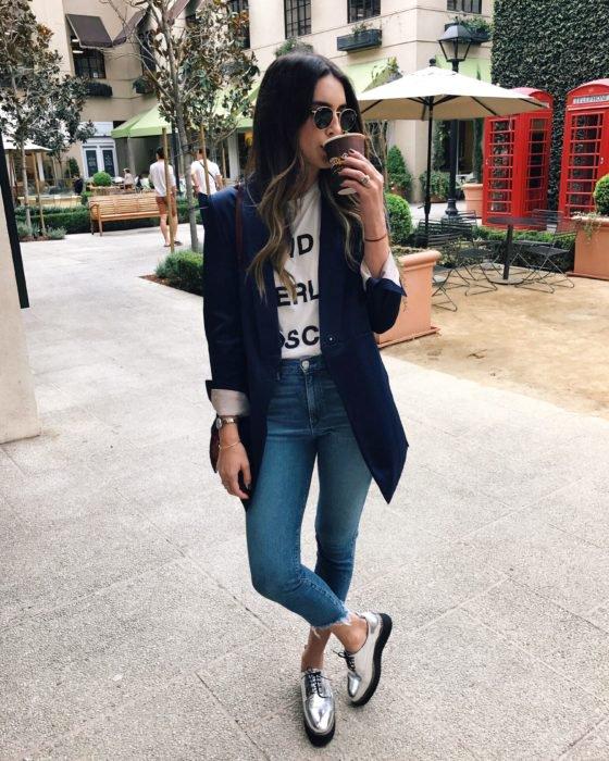 Looks tomboys; chica con atuendo masculino, saco azul marino largo, playera básica blanca, zapatos de plataforma plateados, tomando un café en la calle