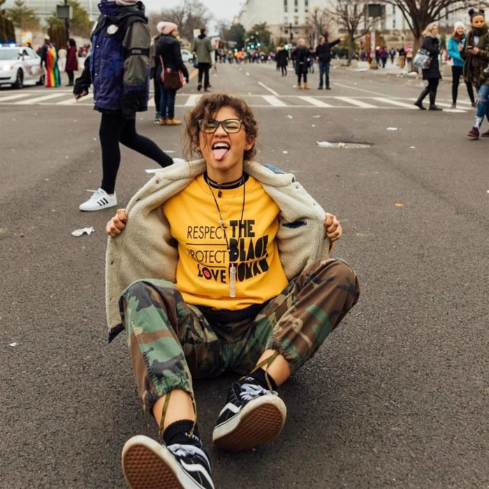 Looks tomboys; chica con atuendo masculino, Zendaya sentada en la calle con pantalón militar, playera amarilla y chamarra de mezclilla con borrega, sacando la lengua