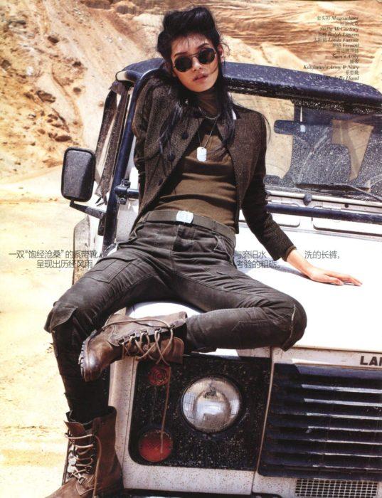 Looks tomboys; chica con atuendo masculino, botas militares, pantalón de mezclilla y saco, sentada en el cofre de una camioneta antigua