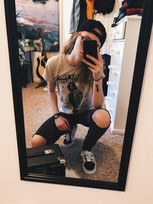 Looks tomboys; chica con atuendo masculino, playera estampada, pantalón de mezclilla desgastado y cachucha,hincada frente a un espejo tomándose una selfie