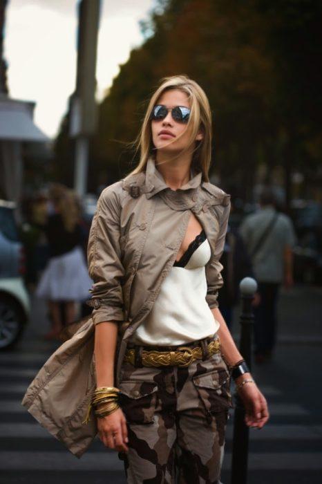 Looks tomboys; mujer con atuendo masculino, pantalón de camuflaje y blusa de seda blanca con encaje y lentes de sol, cruzando la calle