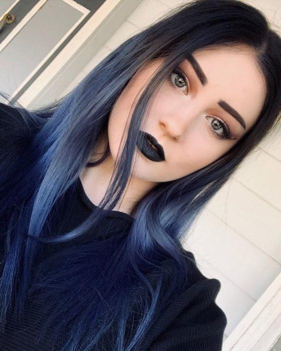 una mujer con cabello oscuro en la parte de arriba de su cabeza, se va aclarando hasta ser azul claro