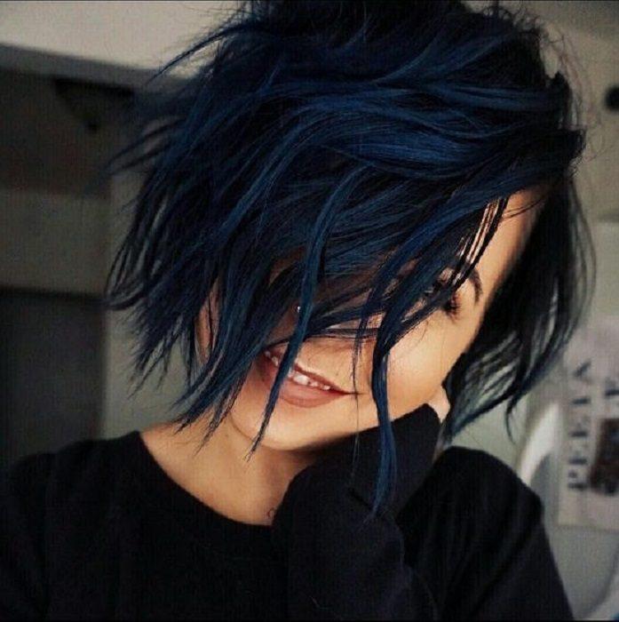 una mujer con pelo negro azulado corto que le cubre la mayor parte de la cara