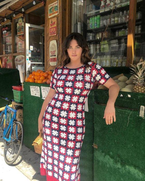 Ali tate Cutler nueva modelo de victoria's secret recargada junto a un puesto de frutas mientras usa un vestido de estampados en color azul y rojo