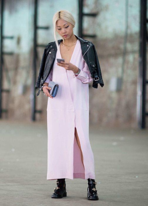 Chica usando un vestido de color rosa, botas y chaqueta de color negra