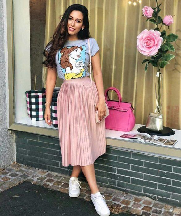 Chica usando una falda de color rosa con una blusa de estampado de la bella y la bestia