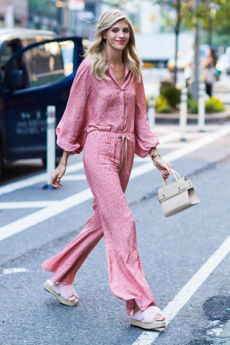 Chica usando un mono de color rosa mientras camina por la calle