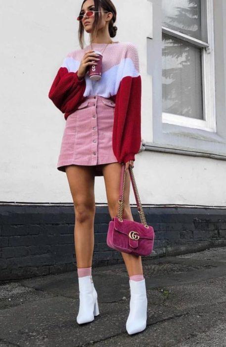 Chica usando una minifalda y un sueter de color rosa y botas blancas