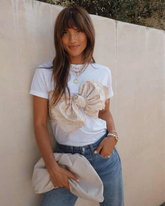 Chica usando una camisa blanca con un moño, jeans y bolso beige mientras está parada sobre una pared