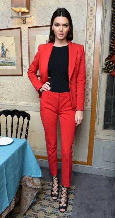 Kendall Jenner usando un traje de color rojo con una blusa de lycra color negra