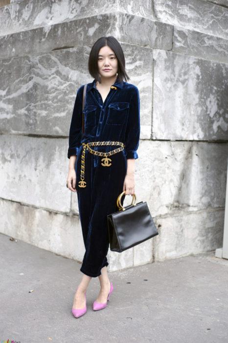 Chica parada en medio de la calle mientras está mostrando su outfit de terciopelo y cinturón de cadena