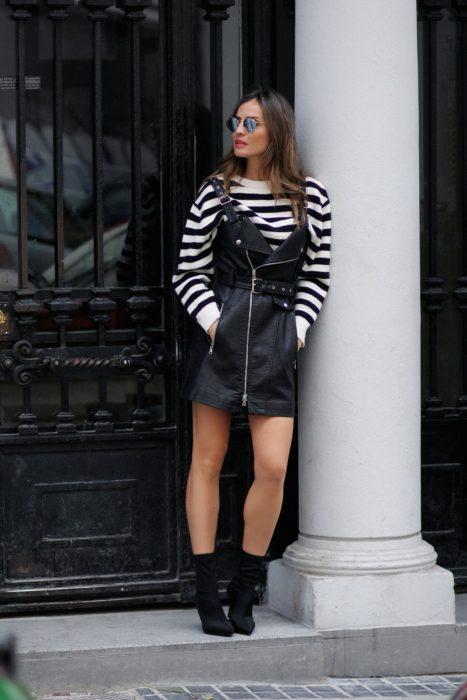 Chica recargada sobre una columna mientras está usando un vestido pichi de cuero negro con una blusa de rayas y botines de color negro