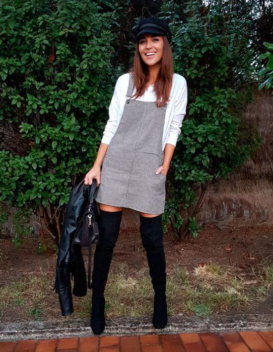 Chica usando un vestido pichi de color gris con botas y boina de color negro