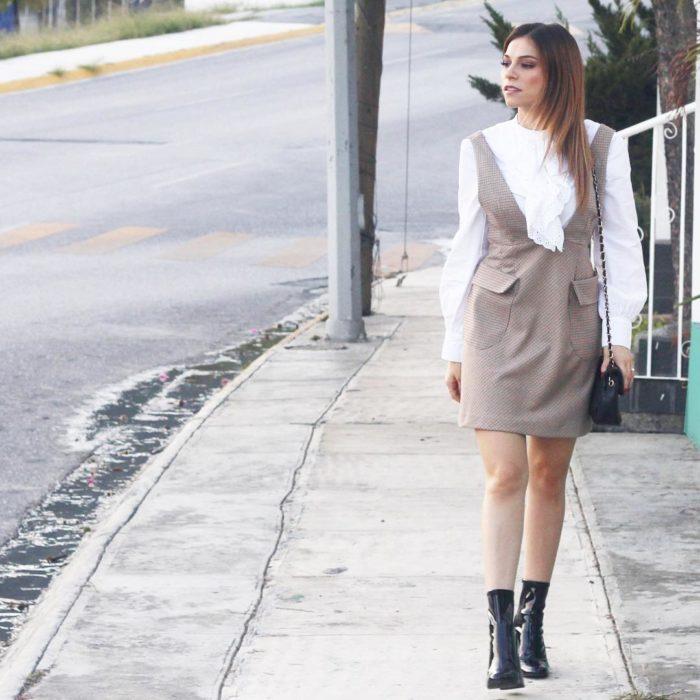 Chica caminando por la calle mientras está usando un vestido de color café y una blusa blanca combinados con unos botines negros