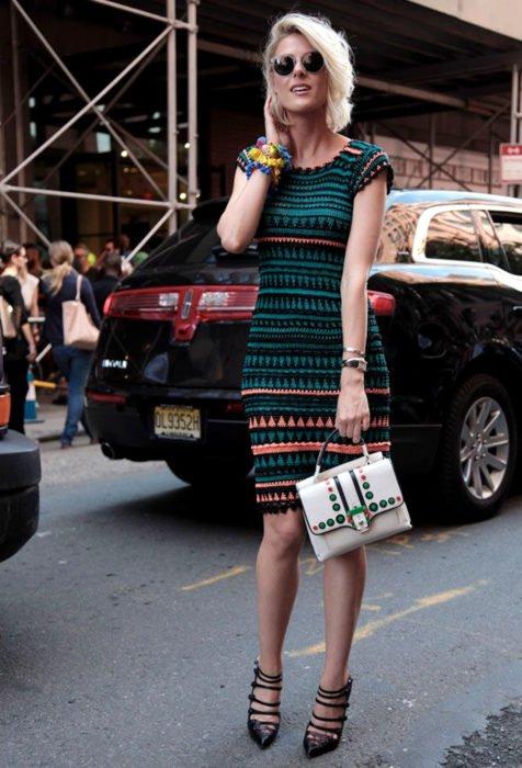 Mujer con lentes de sol, de cabello rubio corto a la moda, con vestido tejido color verde con rayas negras y anaranjadas