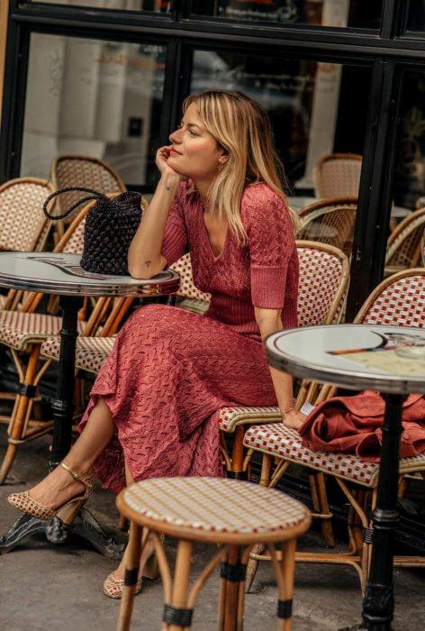 Chica rubia sentada en un café con un vestido rosa tejido