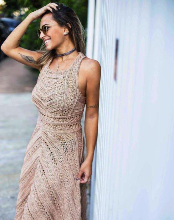 Chica sonriendo con tatuaje de alas en el brazo y vestido beige tejido