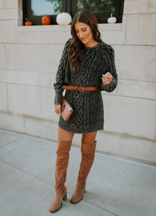 Chica de cabello castaño con vestido gris tejido, con cinto y botas de gamuza café largas arriba de la rodilla