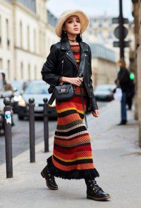 Mujer caminando en la calle, con cabello negro a los hombros, sombrero, maxivestido tejido de colores rojo, anaranjado, amarillo, blando, verde y negro con chaqueta de cuero y botas de trabajo