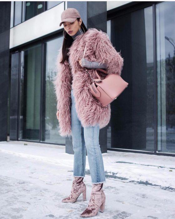 Chica usando un abrigo afelpado de color rosa, botas y gorra