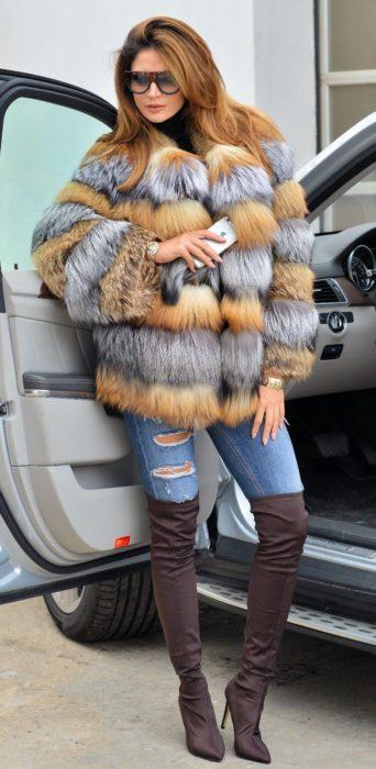 Chica usando un abrigo afelpado de varios colores con jeans y botas de color café