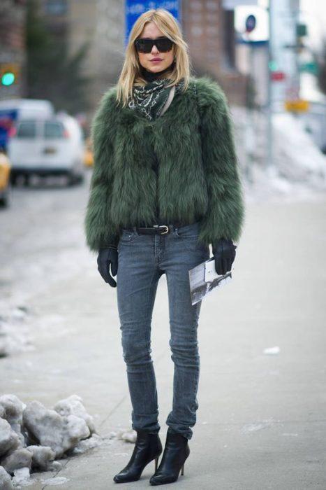 Chica usando un abrigo de color verde militar con jeans y botines