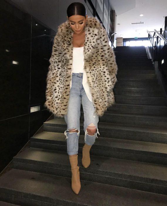 Chica bajando las escaleras mientras usa un abrigo animal print