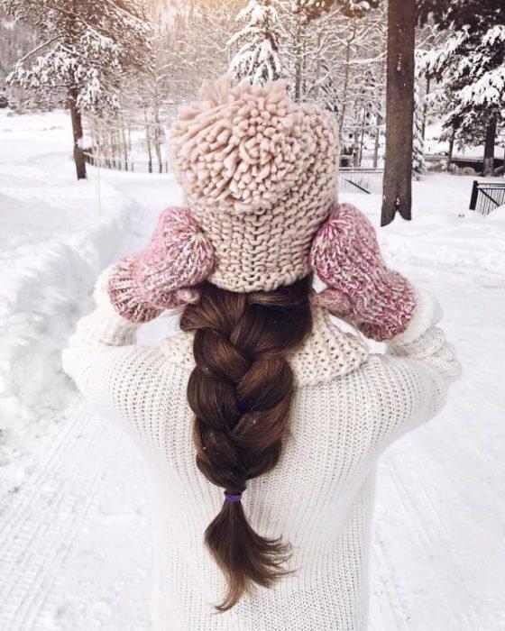 Chica de espaldas mostrando su gorro tejido en color rosa pastel