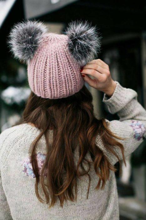 Chica de espaldas llevando un gorrito de estambre con orejas de pompones