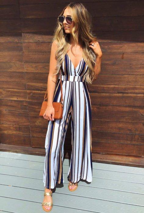 Looks con jumpsuit; chica con lentes del sol, de cabello rubio, largo y ondulado vistiendo un enterizo de tirantes de rayas verticales