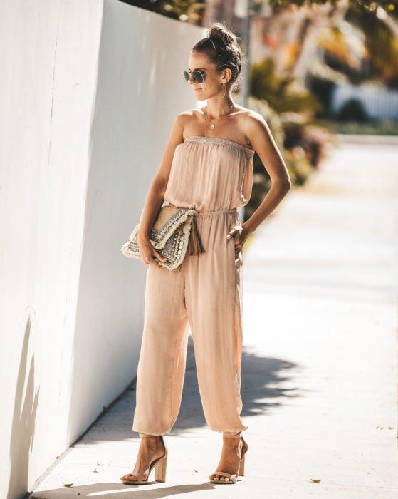 Looks con jumpsuit; mujer peonada con un bun alto, vestida con un enterizo color beige sin hombros y zapatillas de tacones gruesos