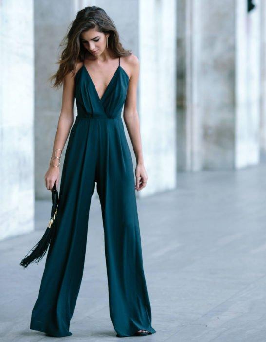 Looks con jumpsuit; chica de cabello castaño y largo con un enterizo de tirantes, holgado de las piernas, color verde