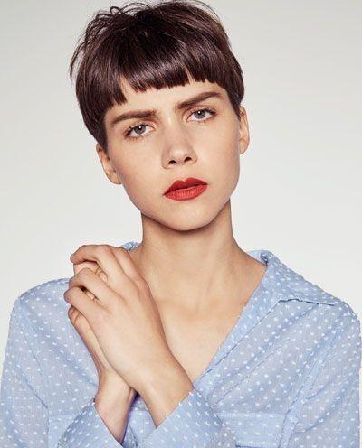 mujer con blusa azul y blanca con corte 'bowl' en color castaño