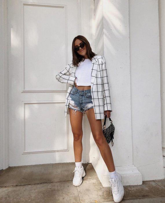 Chica usando shorts con un top blanco, blazer y tenis fila de color blanco