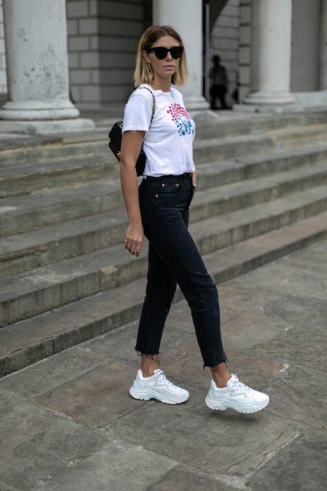 Chica usando un pantalón negro con una blusa y tenis fila de color balncos