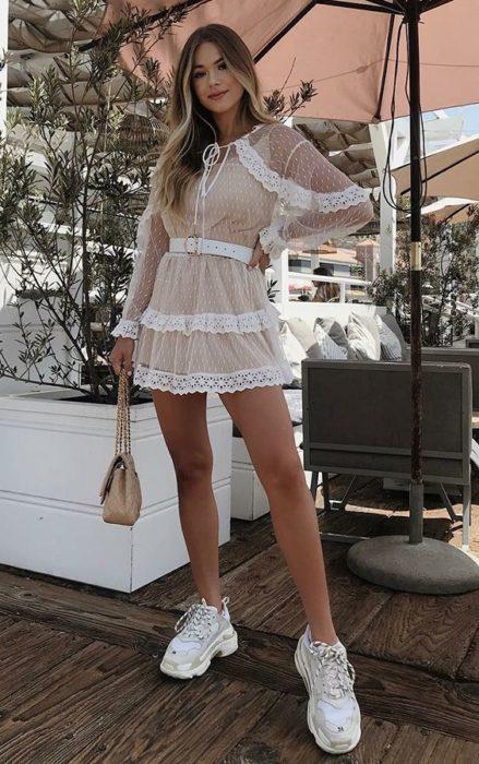 Chica usando un vestido de encaje con unos tenis de color blanco