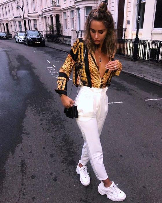 Chica usando unos pantalones de color blanco, blusa de color amarillo y tenis fila de color blanco