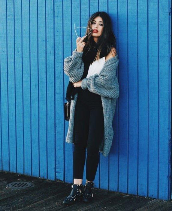 Oversized cardigan; chica de cabello castaño, con suéter holgado tejido color gris con leggins, botines negros con estoperoles, recargada en una pared color azul