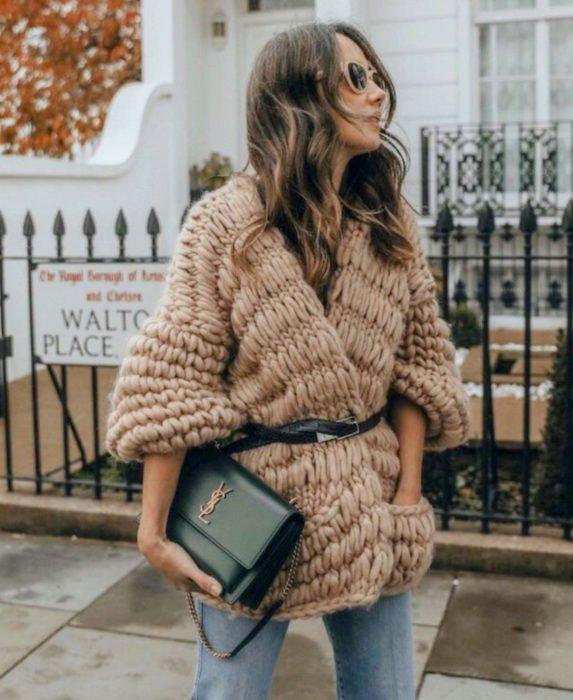 Oversized cardigan; mujer con suéter holgado tejido crochet grueso, con cinto y bolsa de mano negra