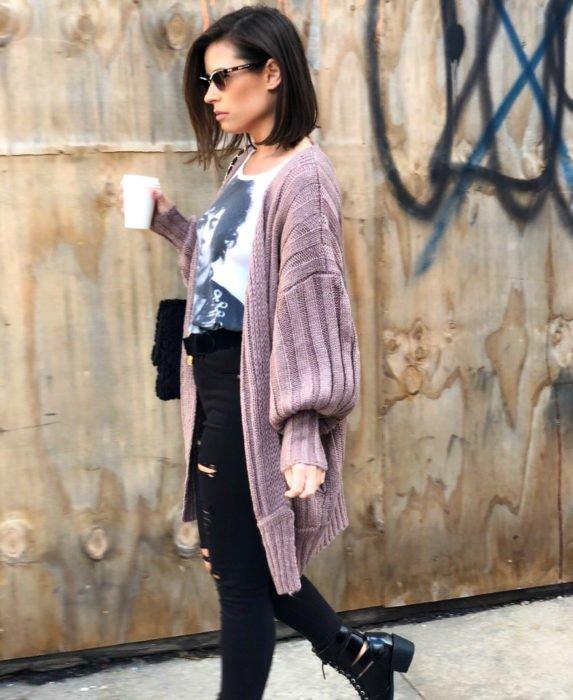 Oversized cardigan; chica caminando en la calle con un vaso de café, mujer de cabello corto, lentes de sol, playera de Prince, suéter holgado rosa tejido
