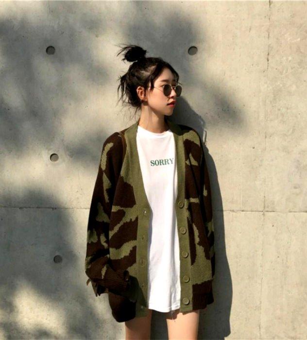 Oversized cardigan; chica coreana con peinado de chongo alto, con lentes de sol y suéter holgado con estampado de camuflaje café y verde